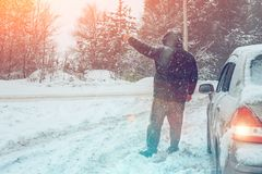 Man near broken car on winter road rises hand asking for help, breakdown of transport on country road in snow blizzard, copy space. Man near broken car on winter royalty free stock photography