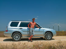 Man near the car. Handsome young man near the car with a naked torso Royalty Free Stock Photos