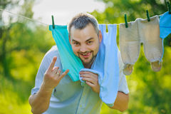 Man near the children's clothing hanging on a rope Stock Images