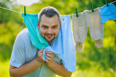 Man near the children's clothing hanging on a rope Stock Photos