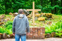 Man near cross at outdoor. In summer day royalty free stock photography