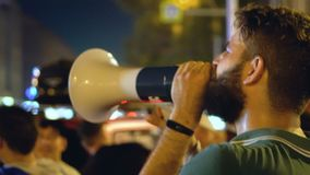 Man near crowd with shout agitates at rally angry man give strong speech. Man near crowd and with mouthpiece agitates at rally. guy in green T-shirt and stock video footage