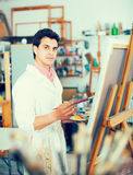 Man near easel painting on canvas. Smiling man with brush near easel painting on canvas Royalty Free Stock Photo