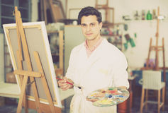 Man near easel painting on canvas. Smiling man with brush near easel painting on canvas Royalty Free Stock Photography