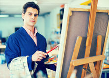 Man near easel painting on canvas. Smiling man with brush near easel painting on canvas Stock Photos