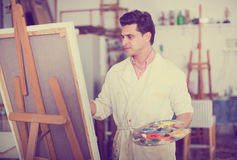Man near easel painting on canvas. Smiling man with brush near easel painting on canvas Stock Photography
