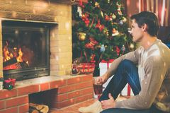 Man near fireplace in Christmas decorated house.  Stock Images