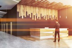 Man near gray office reception. Businessman standing in office hall with gray and wooden walls, concrete floor and white and wooden reception desk. Toned image stock images