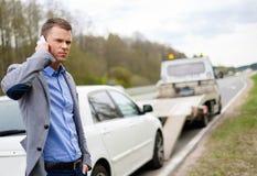 Man near his broken car on a roadside. Man calling while tow truck picking up his broken car Royalty Free Stock Photos