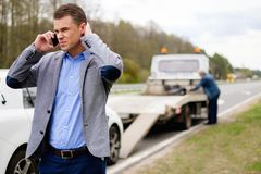 Man near his broken car on a roadside. Man calling while tow truck picking up his broken car Royalty Free Stock Photo