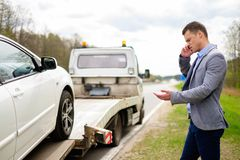 Man near his broken car on a roadside. Man calling while tow truck picking up his broken car Stock Photography