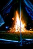 Man near huge camp fire holding lantern Stock Images