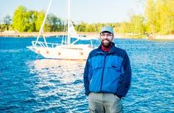 Man near lake. Happy beard man near blue lake and white yacht, sunny day Royalty Free Stock Photos