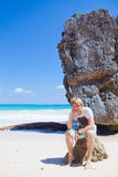 Man near the sea. Young man sitting on the rock near the sea Royalty Free Stock Images