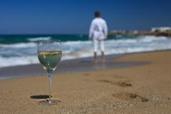 Man near the sea and a glass of wine on the sand Royalty Free Stock Image