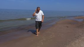 Man near the sea with a shell. In summer day stock video footage