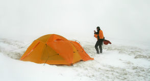 Man near tent in snow blizzard