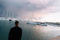A man near the white yachts on the water. Boats on the ocean water. A white yacht. The branches of the tree. Beautiful. Sunset. A pink sunset. Sunset Royalty Free Stock Image