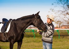 Man nearby horse, striped pullover, blue jeans, hat, close up. Beautiful strong man cowboy nearby black horse. Has happy  face, striped pullover, blue jeans, hat Stock Image