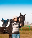 Man nearby horse, striped pullover, blue jeans, hat, close up. Beautiful strong man cowboy nearby black horse. Has happy  face, striped pullover, blue jeans, hat Royalty Free Stock Images