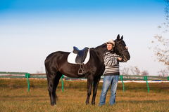Man nearby horse, striped pullover, blue jeans, hat, landscape. Beautiful strong man cowboy nearby black horse. Has happy  face, striped pullover, blue jeans Royalty Free Stock Images
