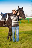 Man nearby horse, striped pullover, blue jeans, hat, landscape. Beautiful strong man cowboy nearby black horse. Has happy  face, striped pullover, blue jeans Stock Photography