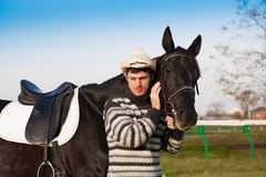 Man nearby horse, striped pullover, hat, smile, close up. Beautiful strong man cowboy nearby black horse. Has happy  smile face, striped pullover, hat. Has sport Stock Images