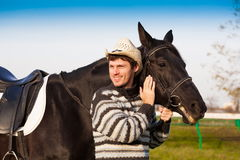 Man nearby horse, striped pullover, hat, smile, close up. Beautiful strong man cowboy nearby black horse. Has happy  smile face, striped pullover, hat. Has sport Royalty Free Stock Image