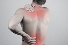 Man with neck and back pain. Man rubbing his painful back close up. Pain relief concept Royalty Free Stock Image