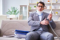 The man in neck brace cervical collar working from home teleworking. Man in neck brace cervical collar working from home teleworking royalty free stock photo
