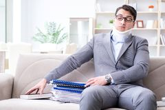 The man in neck brace cervical collar working from home teleworking. Man in neck brace cervical collar working from home teleworking stock photos