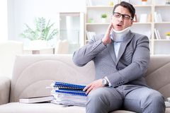 The man in neck brace cervical collar working from home teleworking. Man in neck brace cervical collar working from home teleworking royalty free stock photography