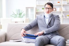 The man in neck brace cervical collar working from home teleworking. Man in neck brace cervical collar working from home teleworking stock photo