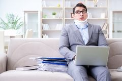 The man in neck brace cervical collar working from home teleworking. Man in neck brace cervical collar working from home teleworking royalty free stock image