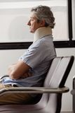 Man With Neck Injury Resting In Lobby. Side view of mature man with neck injury resting in hospital lobby Stock Photos