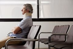 Man With Neck Injury Waiting In Lobby Royalty Free Stock Photography