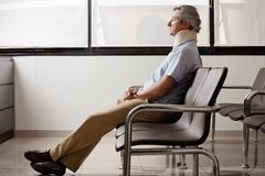 Man With Neck Injury Waiting In Lobby Royalty Free Stock Photos