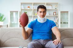 The man with neck injury watching american football at home. Man with neck injury watching american football at home Royalty Free Stock Image
