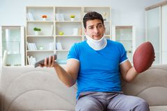 The man with neck injury watching american football at home. Man with neck injury watching american football at home Stock Photo
