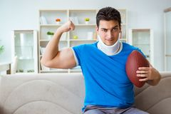 The man with neck injury watching american football at home. Man with neck injury watching american football at home Royalty Free Stock Images