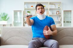 The man with neck injury watching american football at home. Man with neck injury watching american football at home Stock Image