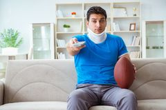 The man with neck injury watching american football at home. Man with neck injury watching american football at home Royalty Free Stock Photos