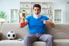 The man with neck injury watching football soccer at home Stock Photos