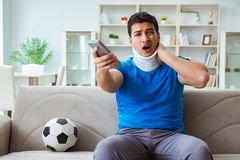 The man with neck injury watching football soccer at home Royalty Free Stock Photo