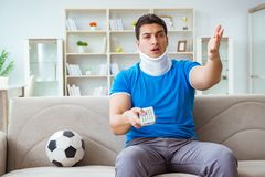 The man with neck injury watching football soccer at home. Man with neck injury watching football soccer at home Royalty Free Stock Image