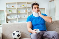 The man with neck injury watching football soccer at home. Man with neck injury watching football soccer at home Stock Image