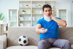 The man with neck injury watching football soccer at home. Man with neck injury watching football soccer at home Stock Photography