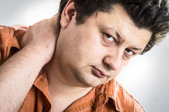 Man with neck pain. Close up portrait of a young man with neck pain stock photography