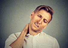 Man with neck pain, after long hours of work Royalty Free Stock Images