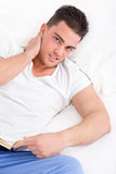 Man with neck pain reading book in bed. Handsome man with neck pain reading book in bed wearing pajamas Royalty Free Stock Photography